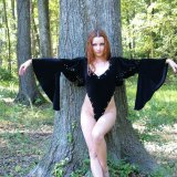 Stripper in black velvet casts sexy magic spell outside in the woods.